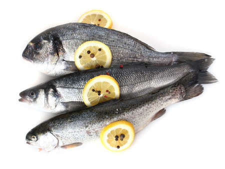 Fresh fishes with lemon and pepper isolated on white photo
