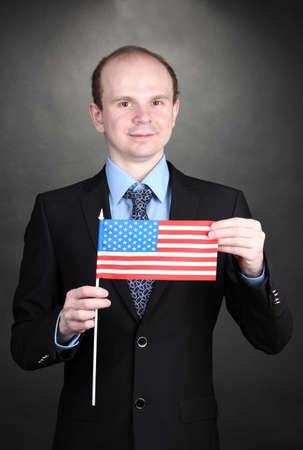 Businessman holding American flag on black background Stock Photo - 13061636