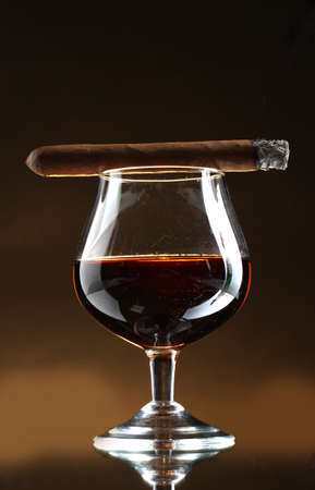 glass of brandy and cigar on brown background Stock Photo - 12913029