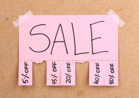 glued: Color advertisement sale on wooden background Stock Photo