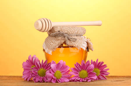Sweet honey in jar with drizzler on wooden table on yellow background photo