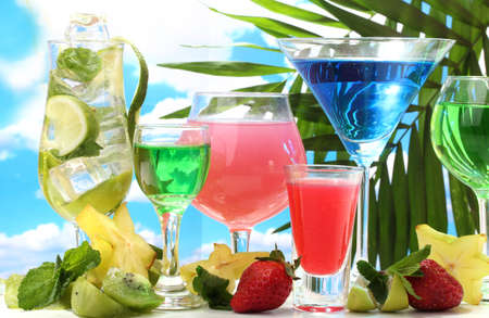 Glasses of cocktails on table on blue sky background photo