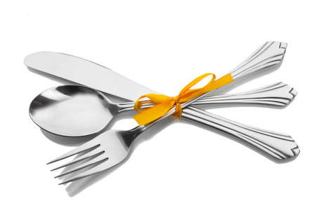 Silver fork and spoon, knife tied with a yellow ribbon isolated on white photo