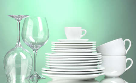 Clean plates, cups and glasses on green background photo