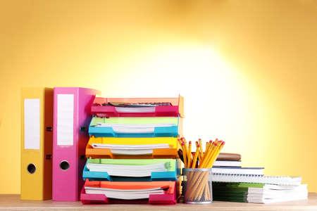 administrative: bandejas de papel brillante y art�culos de papeler�a en la mesa de madera sobre fondo amarillo