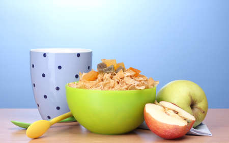 tasty cornflakes in green bowl, apples and glass of milk on wooden table on blue background photo