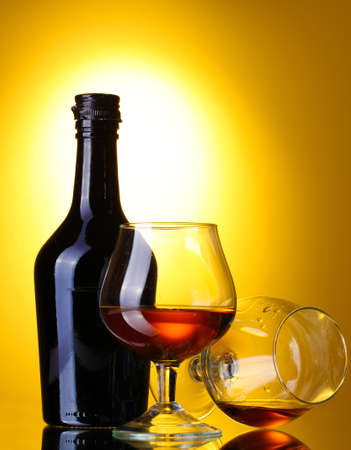 Glasses of brandy and bottle on yellow background photo