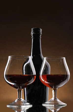 Glasses of brandy and bottle on brown background photo