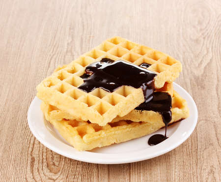 Tasty waffles with chocolate on plate on wooden background Stock Photo - 12980095