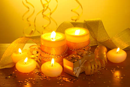Beautiful candles, gifts and decor on wooden table on yellow background Stock Photo
