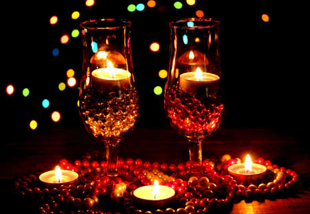 Amazing composition of candles and glasses on wooden table on bright background photo