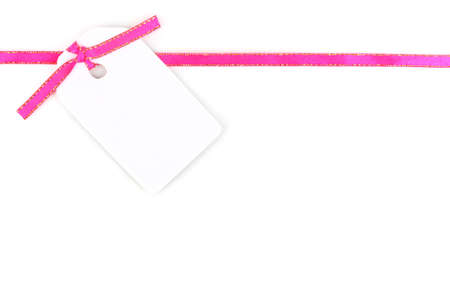 Blank gift tag with pink satin ribbon isolated on white photo