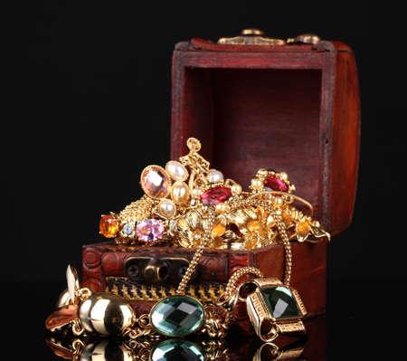 Cassettone in legno piena di gioielli d'oro su sfondo nero Archivio Fotografico
