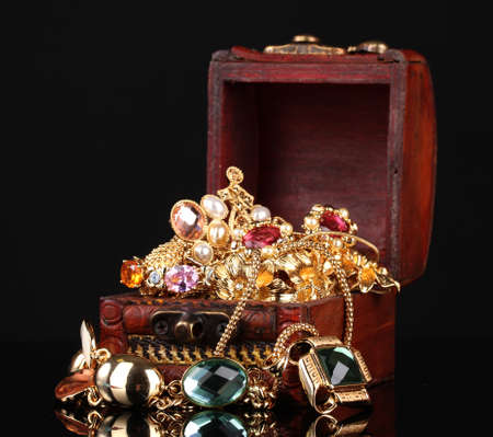 Wooden chest full of gold jewelry on black background Stock Photo - 12980081