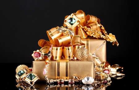 Various gold jewellery and gifts on black background Stock Photo - 12979848