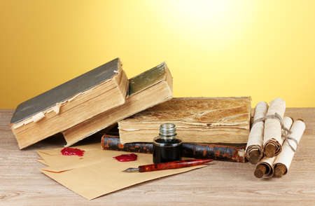 old books, scrolls, ink pen and inkwell on wooden table on yellow background photo