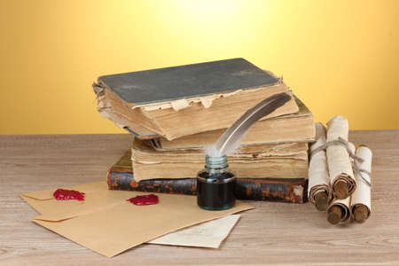old books, scrolls, feather pen and inkwell on wooden table on yellow background photo