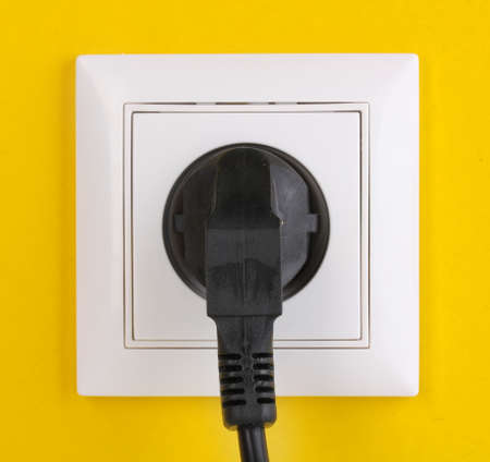 White electric socket with plug on the wall Stock Photo - 12980217