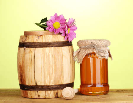 Sweet honey in jar and barrel with drizzler on wooden table on green background photo