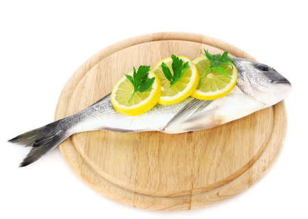 Fresh fish with lemon and parsley on wooden cutting board isolated on white  photo