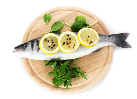 Fresh fish with lemon, parsley and pepper on wooden cutting board isolated on white Stock Photo - 12980076