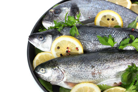 Fresh fishes with lemon, parsley and pepper on plate isolated on white Stock Photo - 12979808