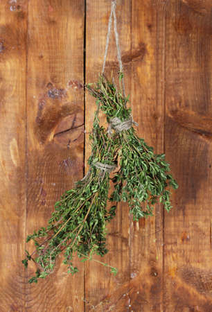 fresh green thyme hanging on rope on wooden background photo