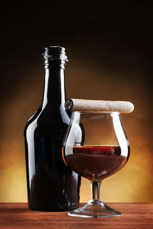 bottle and glass of brandy and cigar on wooden table on brown background Stock Photo - 12980046