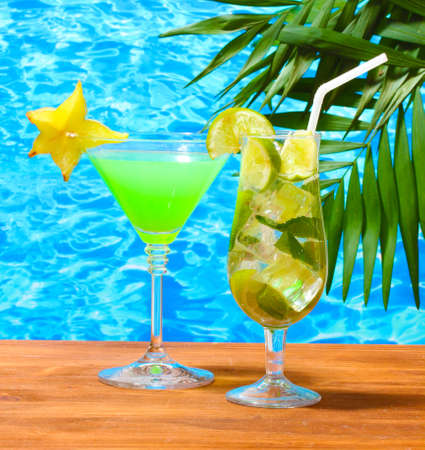 Glasses of cocktails on wooden table on blue sea background Stock Photo - 12979925