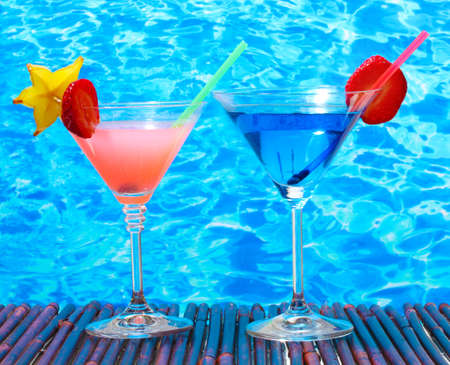 blue hawaiian drink: Glasses of cocktails on table on blue sea background