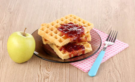 Tasty waffles with jam on plate on wooden background Stock Photo - 12979478