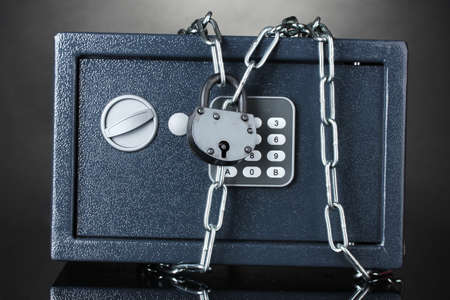safe with chain and lock on grey background Stock Photo - 12979487