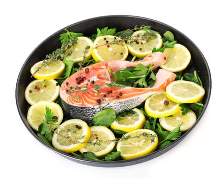 Red fish with lemon, parsley and pepper on plate isolated on white Stock Photo - 12979553