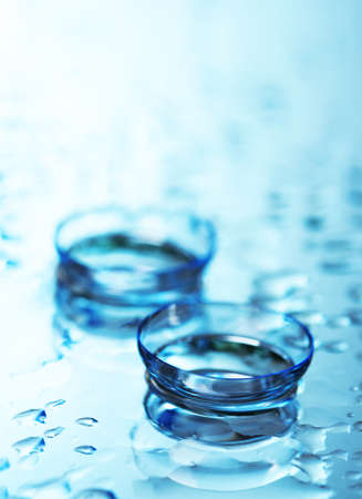 contact lens with drops on blue background photo