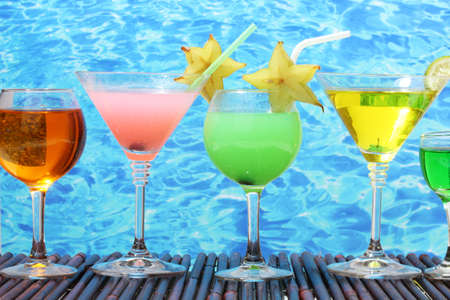 Glasses of cocktails on table on blue sea background photo