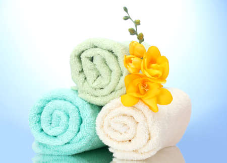 colorful towels and flowers on blue background photo
