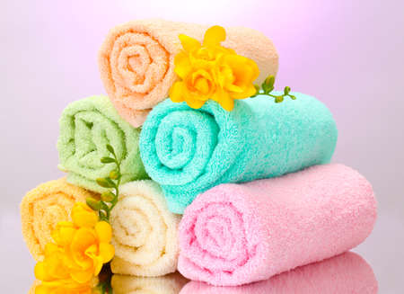colorful towels and flowers on purple background photo