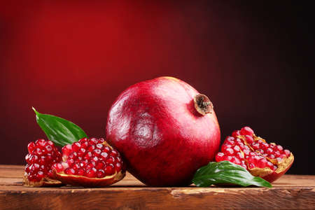 ripe pomegranate fruit with leaves on wooden table on red background photo