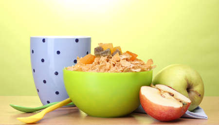 tasty cornflakes in green bowl, apples and glass of milk on wooden table on green background Stock Photo - 13026429