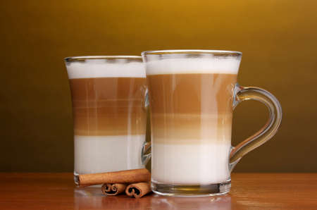 Fragrant сoffee latte in glass cups and cinnamon on wooden table on brown background photo