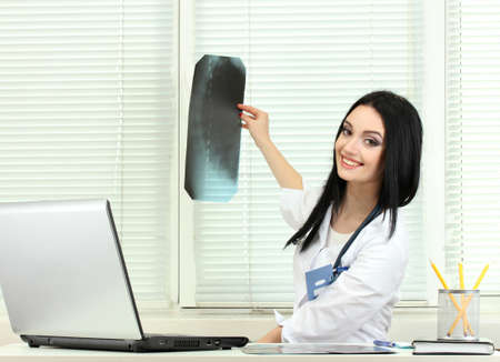 beautiful girl doctor holding X-ray in the office photo