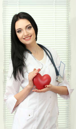 young beautiful doctor with stethoscope holding heart  photo