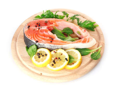 Red fish with lemon and parsley on wooden cutting board isolated on white  photo