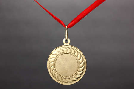 Gold medal on grey background photo