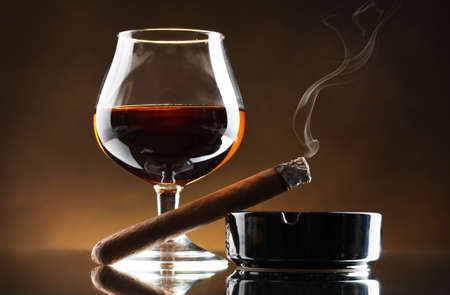 ashtray: glass of brandy and cigar on brown background