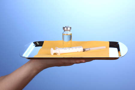 Hand holding tray with syringe and medicines on blue background photo