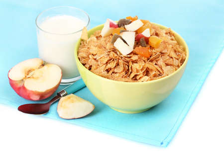 tasty cornflakes in bowl with dried fruits, glass of milk and apple on blue napkin photo