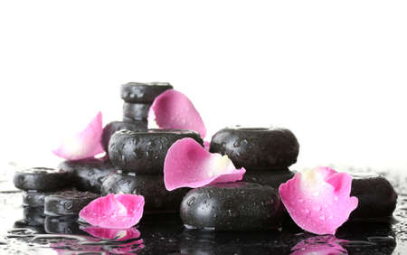 Spa stones with drops and rose petals on white background photo