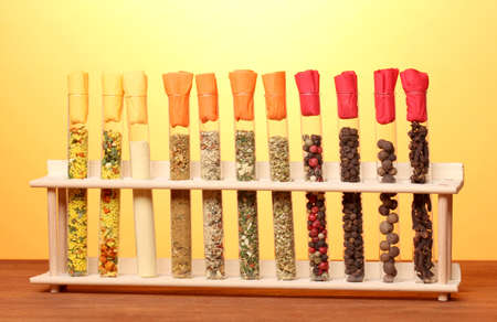 Various spices in tubes on wooden table on yellow background photo
