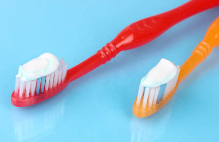 Toothbrushes with paste on blue background photo